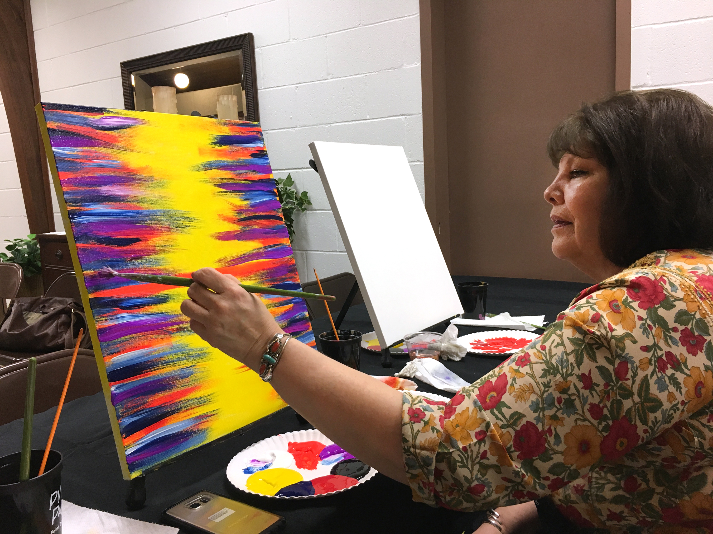 Osage women raise their paint brushes for Family Violence Prevention Awareness